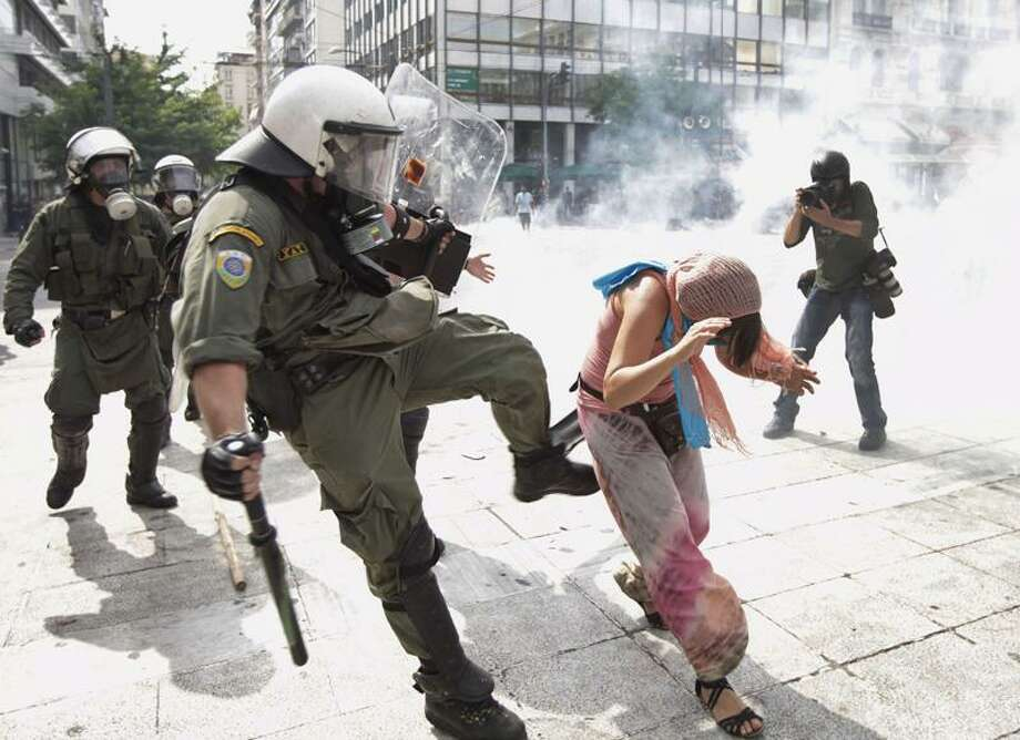 A Greek riot police officer kicks a protester in Athens' main Syntagma square Wednesday. Associated Press Photo: AP / AP