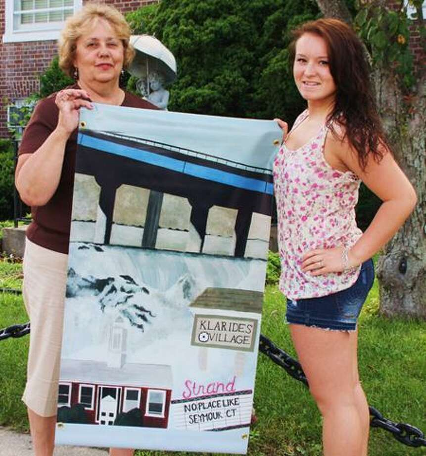 Jean Falbo-Sosnovich/Register Judy Simpson, chairman of the Seymour Culture and Arts Commission, left, displays the prize-winning flag design by Seymour High School senior Demi Gonzalez, right.