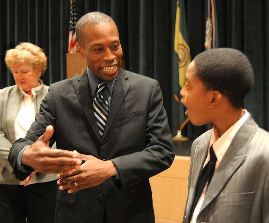 Mayor Scott Jackson-talks with Hamden Middle School seventh-grader Robert Richards after a school meeting in which the mayor announced that Hamden was on the list of the top 100 cities for young people.  Superintendent of Schools, Fran Rabinowitz, is back left. Melanie Stengel/Register