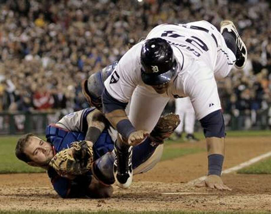 Detroit Tigers Miguel Cabrera is tagged out by Texas Rangers catcher Mike Napoli at home plate during the eighth inning of Game 4 of baseball's American League championship series Wednesday, Oct. 12, 2011, in Detroit. (AP Photo/Charlie Riedel) Photo: AP / AP