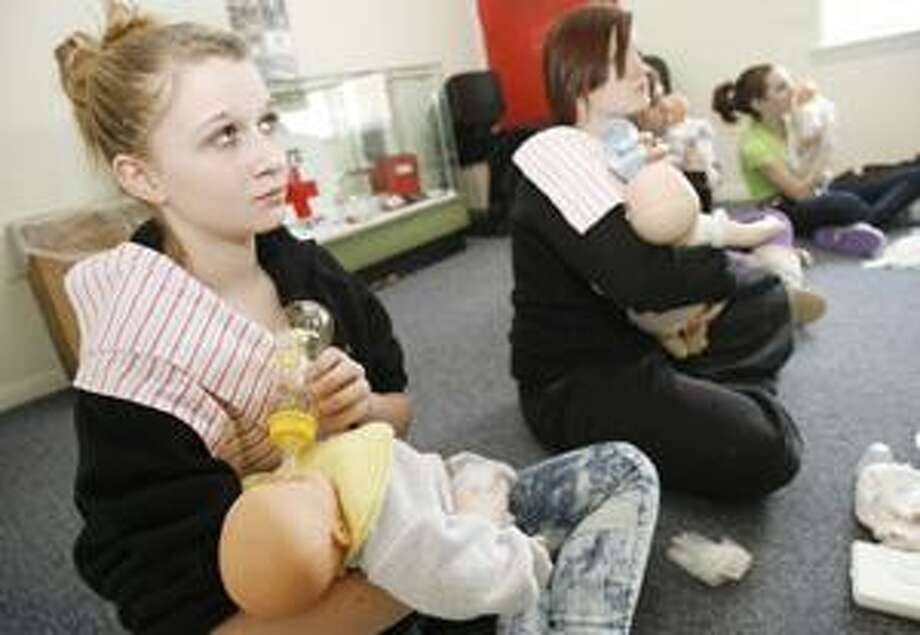 Dispatch Staff Photo by JOHN HAEGER Caitlin Faulkner, 13, of Vernon Center and Emylee Wallis, 14, of Verona, practice feeding and holding a baby during the American Red Cross Baby-sitting Class on Saturday.