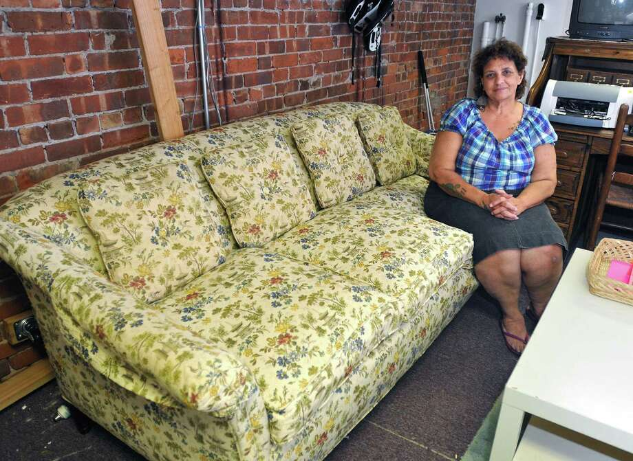 """Dawn Bliesener, owner of """"Clothes Without Borders"""" in Fair Haven, sits on a Federal Style Sofa from the 1920's that was donated from the estate of acclaimed author William Styron. The couch is one of two pieces donated that will benefit """"IRIS,"""" a refugee resettlement organization. The sofa is selling for  $2,500. Peter Casolino/Register"""