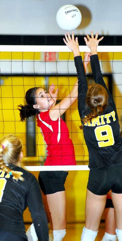 Tara Dering (left) of Branford and Caitlyn Strona (right) of Amity fight for the point during Branford's four-set win. Photo by Arnold Gold/New Haven Register