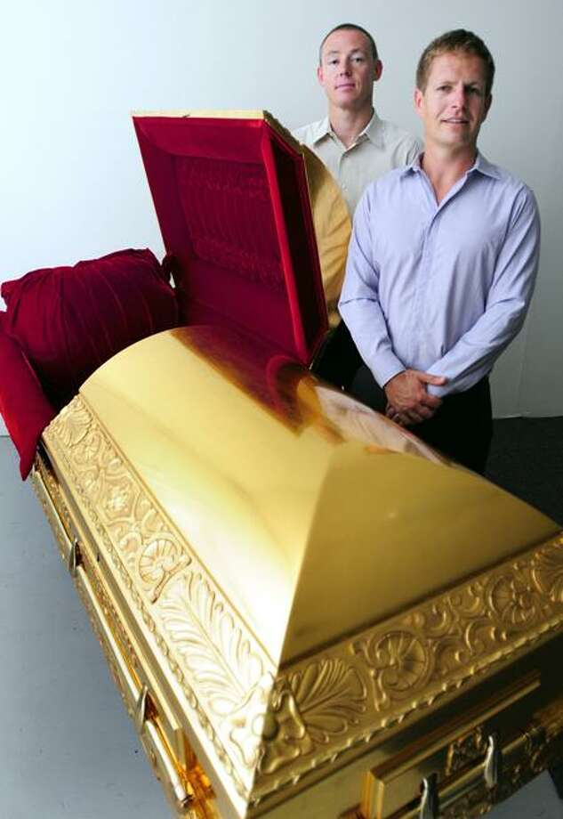 Arnold Gold/Register photos: Edward Balfour, vice president, left, and Justin Wessels, president of The Golden Casket in Old Saybrook, show one of their sculpted cherry wood caskets covered in double-gilded, 24-karat gold.