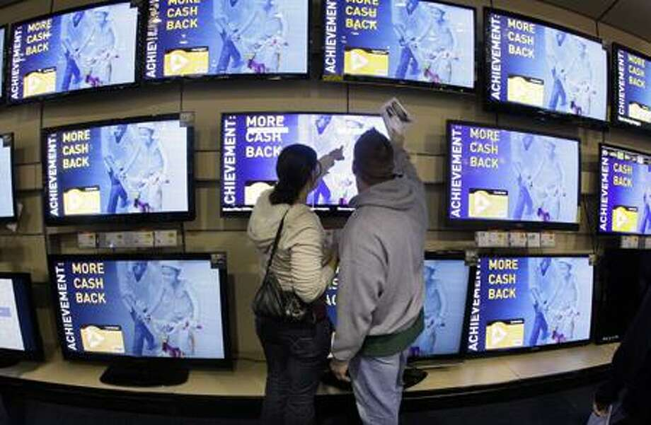 Shoppers look at televisions displayed at a Best Buy store in Brentwood, Tenn., Nov. 25. Companies decreased their overall orders to U.S. factories in October for the second straight month. (Associated Press) Photo: AP / AP2011
