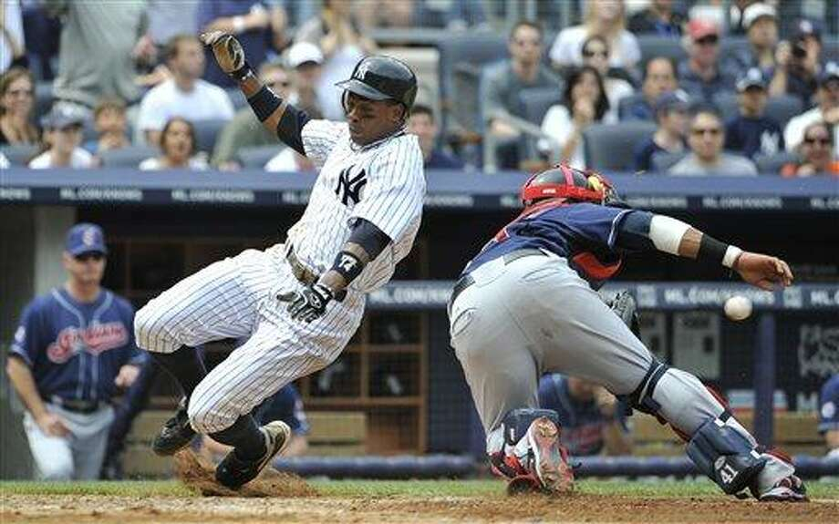 New York Yankees' Curtis Granderson beats the throw to Cleveland Indians catcher Carlos Santana to score on a two run double by Alex Rodriguez in the fifth inning of a baseball game Sunday, June 12, 2011, in New York. (AP Photo/Kathy Kmonicek) Photo: AP / FR170189 AP