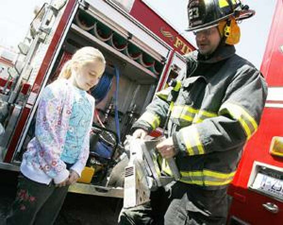 Photo by JOHN HAEGER Lexi Matteson, 10, of Madison, watches as Madison Firefighter Dave Settle explains about some of the equipment that is used in the fire services during an open house of the department on Saturday, April 9, 2011 in Madison.
