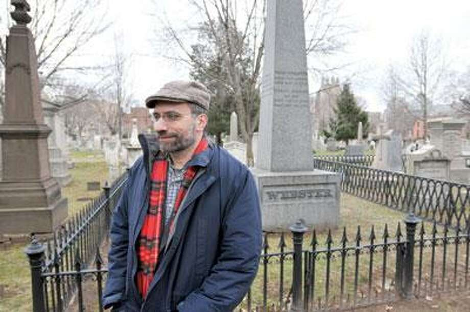 Author Joshua Kendall stands next Webster's grave in New Haven's Grove Street Cemetery. (Peter Casolino/ Register)