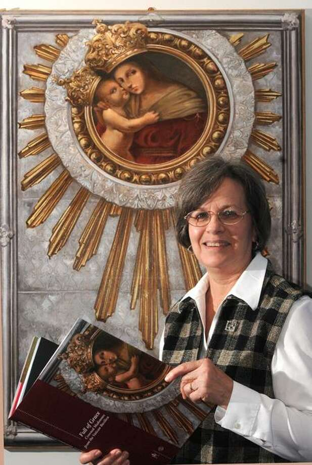 "Mary Lou Cummings, curator at the Knights of Columbus Museum in New Haven, stands with ""Madonna Avvocata del Popolo,"" a crowned image of Mary based on a 16th-century oil on wood painting from Italy. It is part of the museum's exhibition of Marian images on loan from the Vatican."