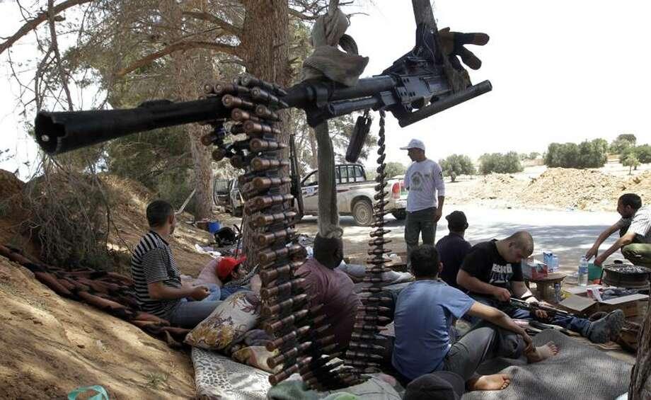 Rebels rest before attacking Gadhafi troops on the frontline of Dafneya near Misrata, Libya, Saturday.  Associated Press Photo: ASSOCIATED PRESS / AP2011