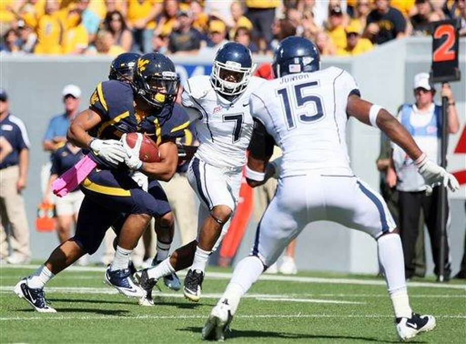 """West Virginia running back Dustin Garrison (29) carries the ball in for a rushing touchdown as Connectictut Dwayne Gratz (7) and Jerome Junior (15) attempt to keep him out during the second quarter of an NCAA college football game on Saturday, Oct. 8, 2011, in Morgantown, <a href=""""http://W.Va"""">W.Va</a>. (AP Photo/Chris Jackson) Photo: AP / FR170573 AP"""