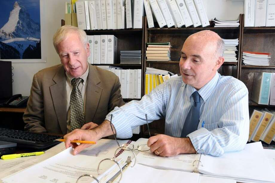 Outgoing Milford Deputy Superintendent of School Operations Philip Russell, left, works on the budget with his replacement, former Mayor James L. Richetelli Jr. Peter Casolino/New Haven Register   11/30/11