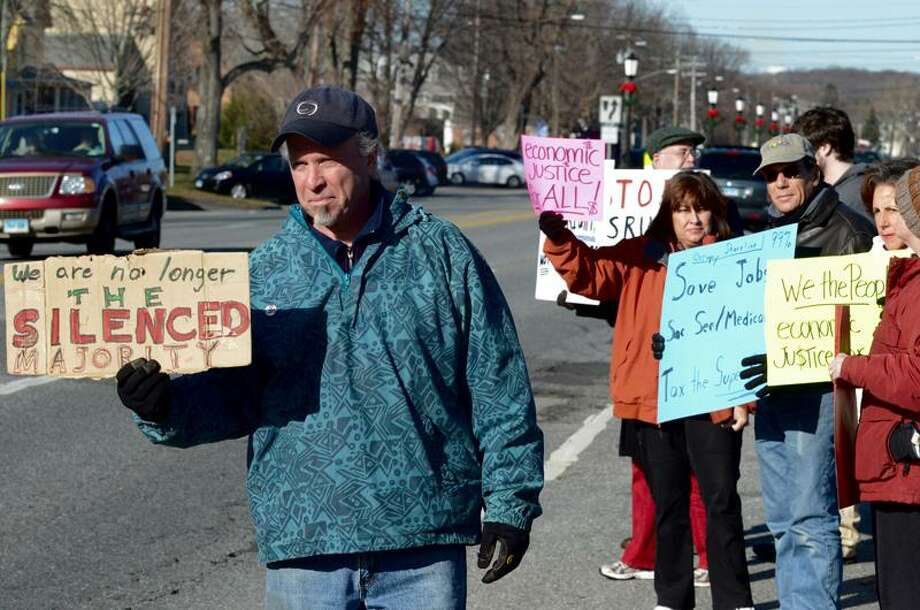 Michael Harreis holds a sign out to passing motorists on Main Street in Old Saybrook Saturday during the Occupy Old Saybrook protest. VM Williams/Register