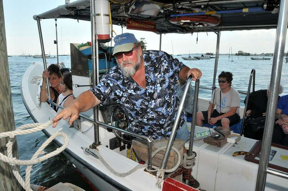 "Capt. Dave Kusterer casts off as he prepares to take a sightseers out on the ""Thimble Islander"" for a tour of Branford's Thimble Islands Thursday. Peter Casolino/Register"