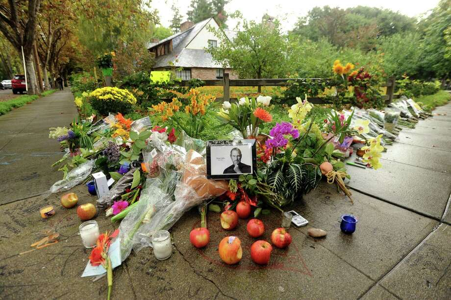 A memorial covers a sidewalk in front of Steve Job's Palo Alto, Calif., home Thursdayy. (AP Photo/Noah Berger) Photo: ASSOCIATED PRESS / AP2011