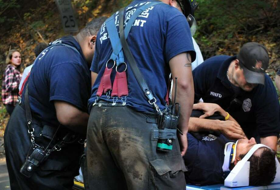 NEW HAVEN-A hiker who was injured climbing East rock (L) looks on as one of the firefighters who was injured trying to rescue her is prepared for ambulance transport.    Melanie Stengel/Register