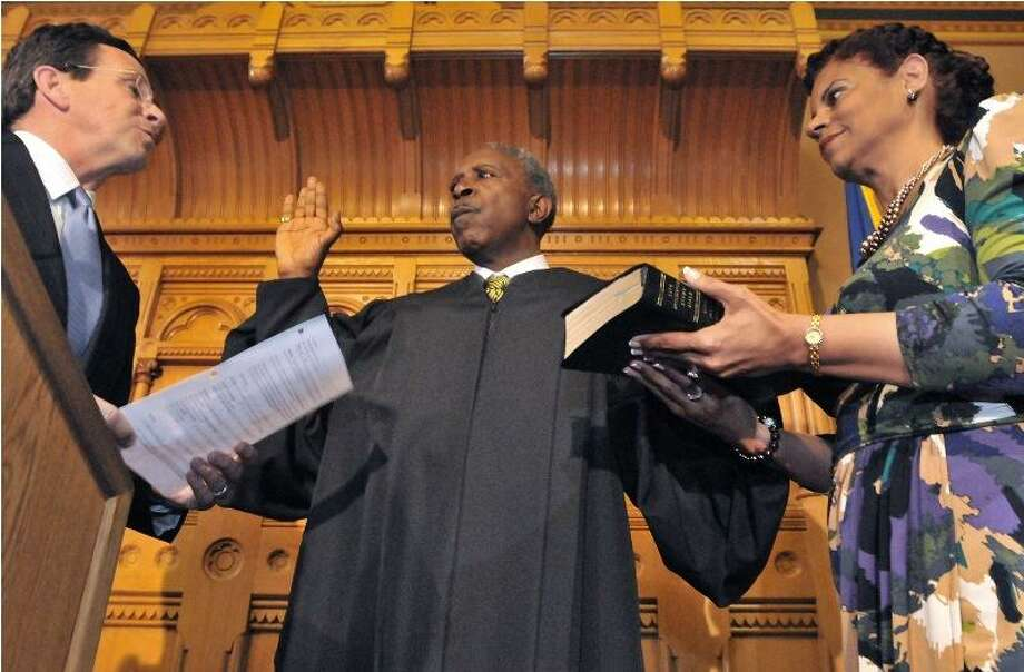 Hartford -- New Haven native, Judge Lubbie Harper Jr. is sworn in to the Connecticut Superior Court by Gov. Dannel P Malloy, left, at the State Capitol Friday. Harper's wife Twila Harper, right, holds the Bible. Photo by Brad Horrigan/New Haven Register