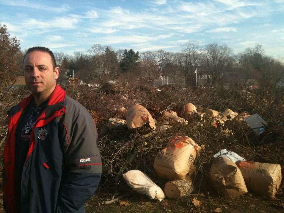 Assistant Public Works Director Michael Siciliano assesses the illegal dumping at Frank Cesare Memorial Field in Hamden. Ann DeMatteo/Register