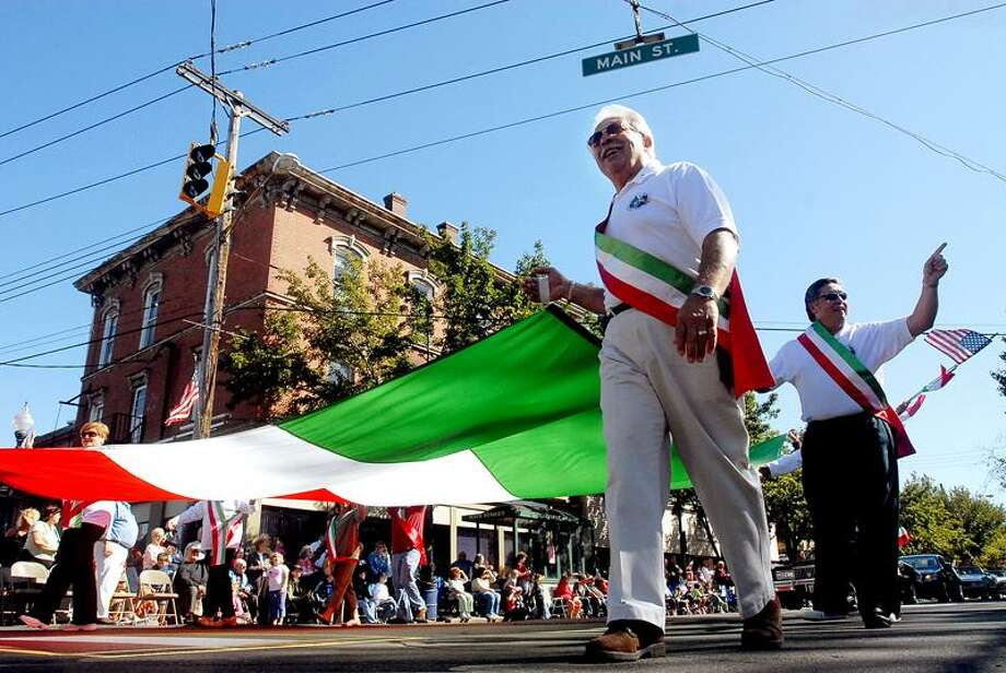 Register file photo: When the Columbus Day Parade last stepped off in 2006 in West Haven, Greater New Haven Columbus Day committee members Anthony Tata of North Haven, left, and Nick Casella of Hamden walked the parade route holding an Italian flag along Campbell Avenue.