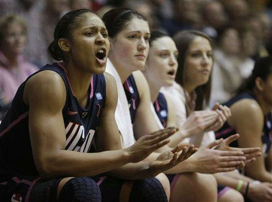 Connecticut forward Maya Moore, left to right, center Stefanie Dolson, guard Kelly Faris and guard Caroline Doty cheer on their team during the second half of an NCAA basketball game against Providence at Alumni Hall on the Providence College campus in Providence, R.I., Saturday afternoon, Feb. 12, 2011. Connecticut's starters sat on the bench most of the second half as they defeated Providence 68-38. (AP Photo/Stephan Savoia) Photo: AP / AP