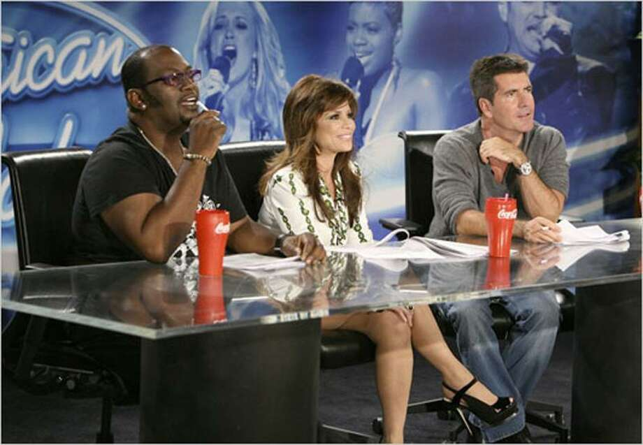 """""""American Idol"""" judges sit at a desk with drinks strategically placed in front of them."""