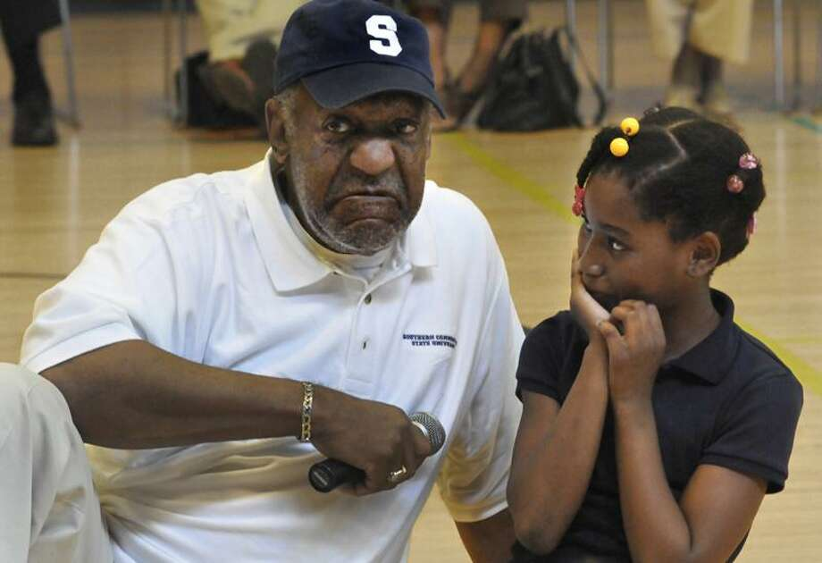 "Bill Cosby makes a face as Annabel Obas, 8, challenges his ""correct"" answer to a math problem at Beecher Interdependent Museum Magnet School of Arts and Sciences in New Haven Thursday. Melanie Stengel/Register"