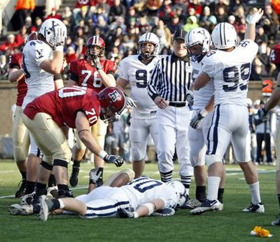 Yale Bulldogs outside line backer Jesse Reising (10) lines on the turf with Harvard Crimson running back Gino Gordon (22) ,background, moments after they had a helmet to helmet hit during the second half of a NCAA college football game on Saturday, Nov. 20, 2010 in Cambridge, Mass. Gordon eventually walked off but Reising, who has signed up for the Marine Corps Officer Candidate School, was wheeled off on a stretcher. There was no immediate word on Reising's condition.  Harvard won 28-21.   (AP Photo/Greg M. Cooper) Photo: AP / FR6006 AP