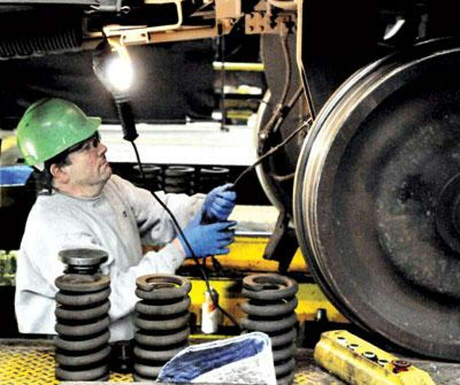 Sheet metal worker Brian McNamara removes ductwork from a Metro-North train in the New Haven rail yard. (Melanie Stengel/Register)