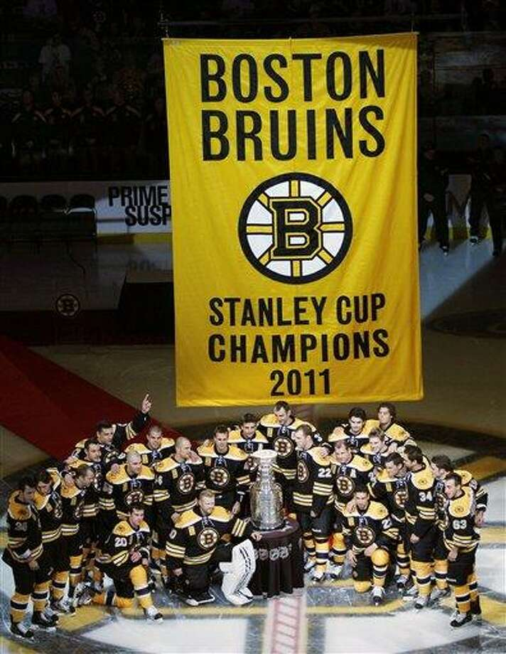 Boston Bruins players pose with the Stanley Cup and championship banner prior to facing the Philadelphia Flyers on opening night in an NHL hockey game in Boston, Thursday, Oct. 6, 2011. (AP Photo/Charles Krupa) Photo: AP / AP