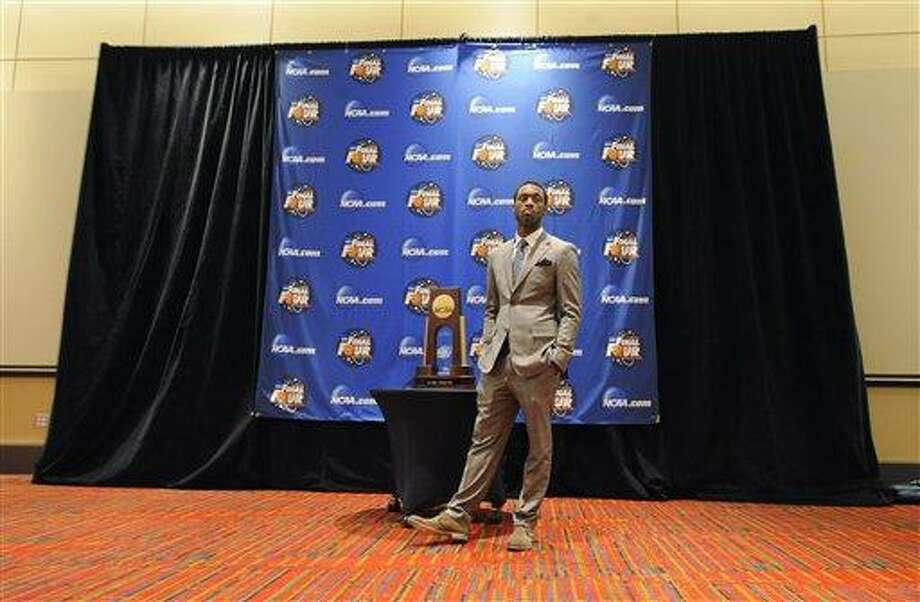 Former Connecticut basketball player Kemba Walker stands next to the NCAA championship trophy while he waits for pictures with fans in Hartford, Conn., Thursday, Oct. 6, 2011. The 2010-11 Huskies received their national championship rings. (AP Photo/Jessica Hill) Photo: AP / AP2011