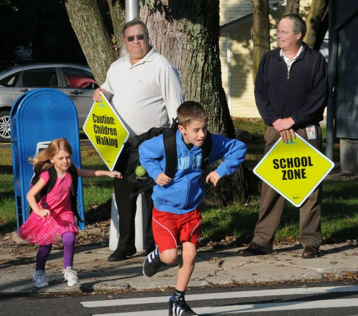 Skyler Kinsella, left, and brother Jimmy Kinsella cross the street on their way to Anna LoPresti School in Seymour. Helping them to cross safely are Mike Shannon, left, and Paul Sobolewski of FedEx. This is part of International Walk to School Day. Melanie Stengel/Register
