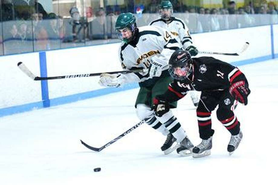 Hamden-- Hamden's Zak Masotta battles for the puck with New Canaan's Charlie Corcoran during the second period. Photo by Peter Casolino/New Haven Register02/11/11 Cas110211