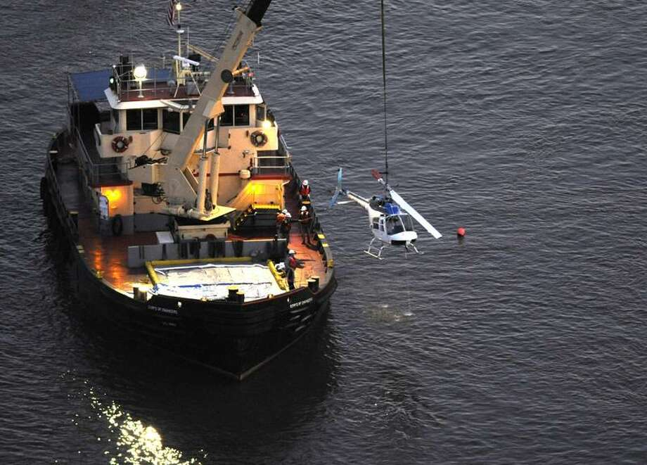 A helicopter that crashed into the East River in New York is raised from the water. The helicopter with five people aboard crashed into the river Tuesday afternoon after taking off from a launch pad on the riverbank, killing one passenger and injuring three others. Associated Press