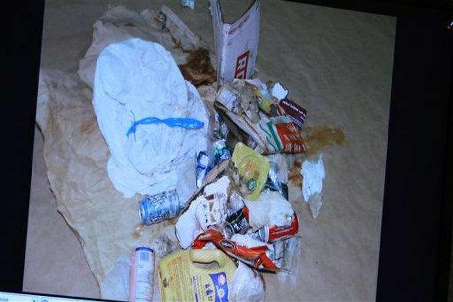 A photo entered into evidence is seen on a courtroom monitor during the Casey Anthony murder trial at the Orange County Courthouse on Tuesday, June 7, 2011, in Orlando, Fla. The photo shows the contents of a bag of trash that was found in the trunk of Anthony's car. Anthony is charged with killing her 2-year old daughter in 2008. (AP Photo/Joe Burbank,Pool) Photo: AP / Pool Orlando Sentinel