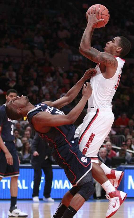 St. John's Dwight Hardy, right, scores as he is fouled by Connecticut's Kemba Walker in the second half of an NCAA college basketball game Thursday, Feb. 10, 2011, in New York. Hardy scored 33 points as St. John's won the game 89-72. (AP Photo/Frank Franklin II) Photo: AP / AP