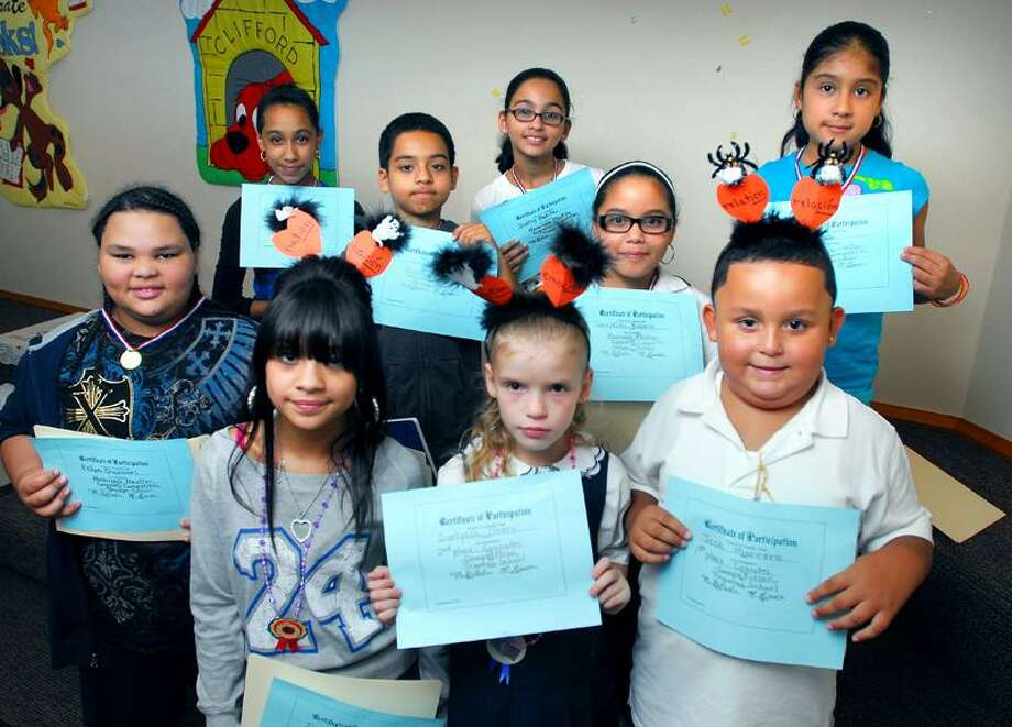 Winners of the Cognates Competition pose Tuesday with their certificates at Truman School in New Haven. In the front row, from left, are Ivelisse Hernandez (third), Carlyssa Otero (second), Jose Marrero (first) and honorable mention award recipients in the back row, from left, are Felipe Quinones, Eleena Rodriguez, Desiny Padilla, Janeyshka Rosario, Daniel Sein and Kelly Pinos.   Arnold Gold/Register