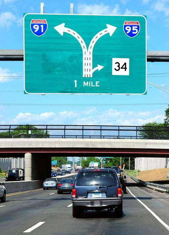 Cars pass under a new sign for the Route 34 flyover ramp in New Haven Monday. (Arnold Gold/Register)