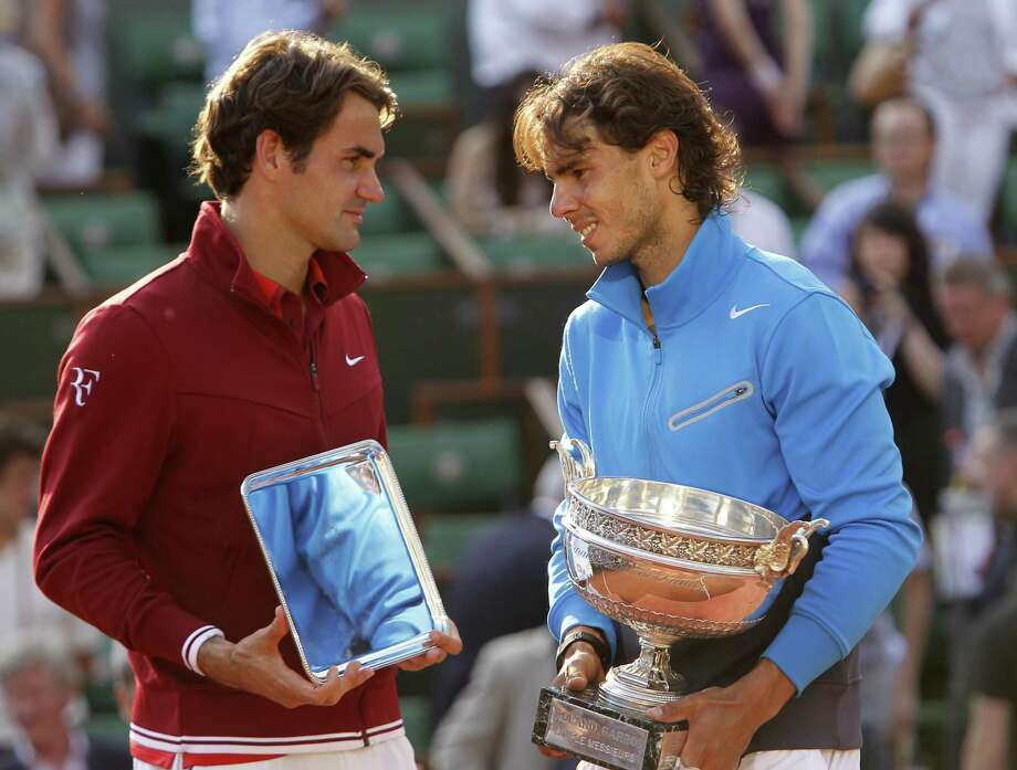 Spain's Rafael Nadal, right, and  Switzerland's Roger Federer pose with their trophies after the men's final match for the French Open tennis tournament at the Roland Garros stadium, Sunday, June 5, 2011, in Paris.  (AP Photo/Lionel Cironneau) Photo: ASSOCIATED PRESS / AP2011