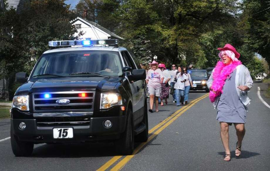"In the home stretch, Seymour Selectman Kurt Miller sprints past the pace car on his way to the finish line. Milller was part of Seymour Pink's ""Walk a Mile in Her Shoes"" fundraiser.  Melanie Stengel/Register"
