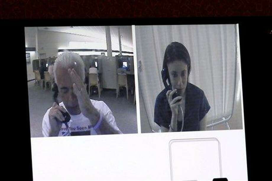 A courtroom monitor shows Casey Anthony, right, talking with her father George Anthony while she was in jail in a video presented as evidence in the Casey Anthony trial at the Orange County Courthouse, Friday, June 3, 2011 in Orlando. The tapes document jail-house conversations between her and her parents after she had been detained following the disappearance of her daughter Caylee. Anthony, 25, is charged with killing her daughter Caylee in the summer of 2008. (AP Photo/Red Huber, Pool) Photo: AP / AP2011