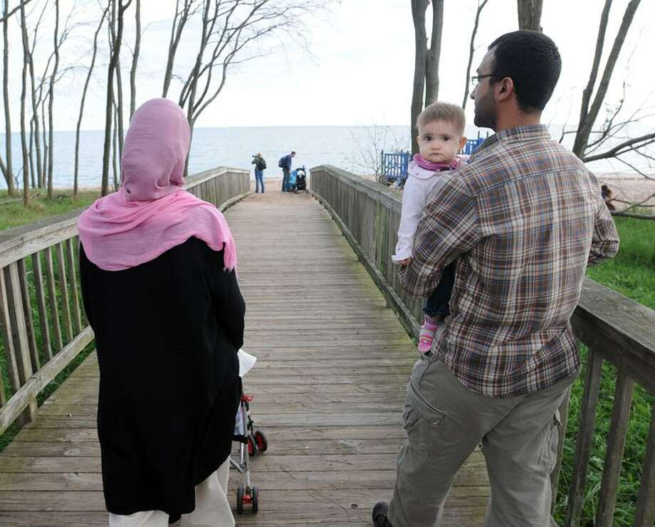Mohamed Elsamra, with his 11-month-old daughter Khadija Elsamra and wife, Tracy Hunsberger, take a break after finishing the  IWAGEPEACE walk that brings Christians, Jews and Muslims together to promote peace. The event was held on the West Haven boardwalk near Grove Park.  Peter Casolino/New Haven Register