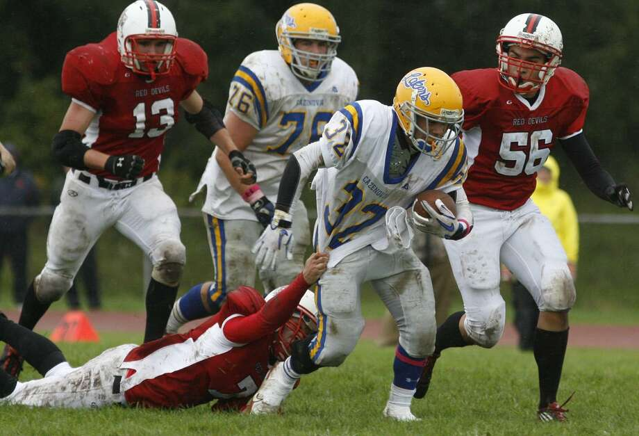"Dispatch Staff Photo by JOHN HAEGER<a href=""http://twitter.com/oneidaphoto"">twitter.com/oneidaphoto</a>Cazenovia's  Jake Wilson (32) battles to break the tackle of VVS Eli Cleveland (7)  in the first half of the game  on Saturday, Oct. 1, 2011in Verona"
