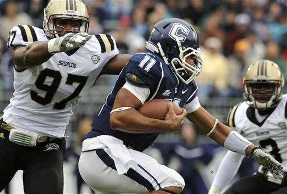 Connecticut quarterback Scott McCummings (11) runs the ball with pressure from Western Michigan's Freddie Bishop (97) in the first quarter of an NCAA college football game, in East Hartford, Conn., on Saturday, Oct. 1, 2011. (AP Photo/Jessica Hill) Photo: AP / AP2011