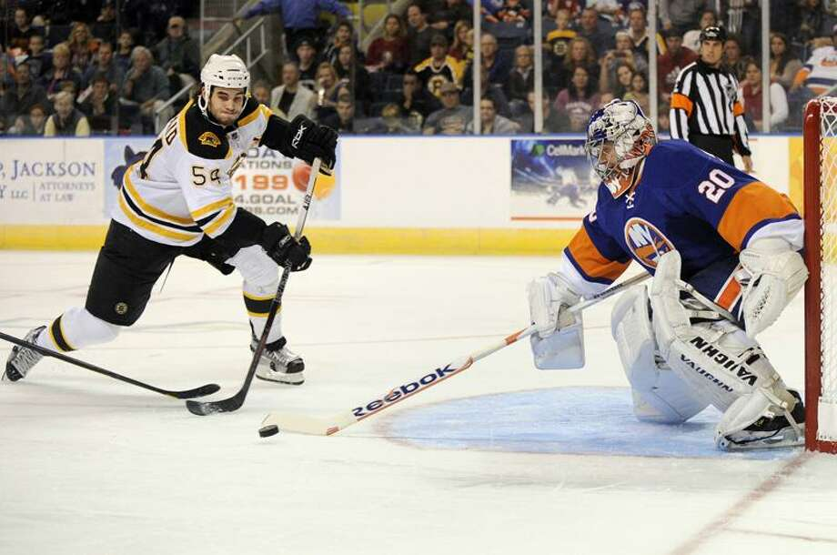 Boston Bruins' Adam McQuaid, left, drives to the net as New York Islanders' Evgeni Nabokov makes a save during the second period of a preseason NHL hockey game in Bridgeport, Conn., on Saturday, Oct. 1, 2011. (AP Photo/Fred Beckham) Photo: AP / FR153656 AP