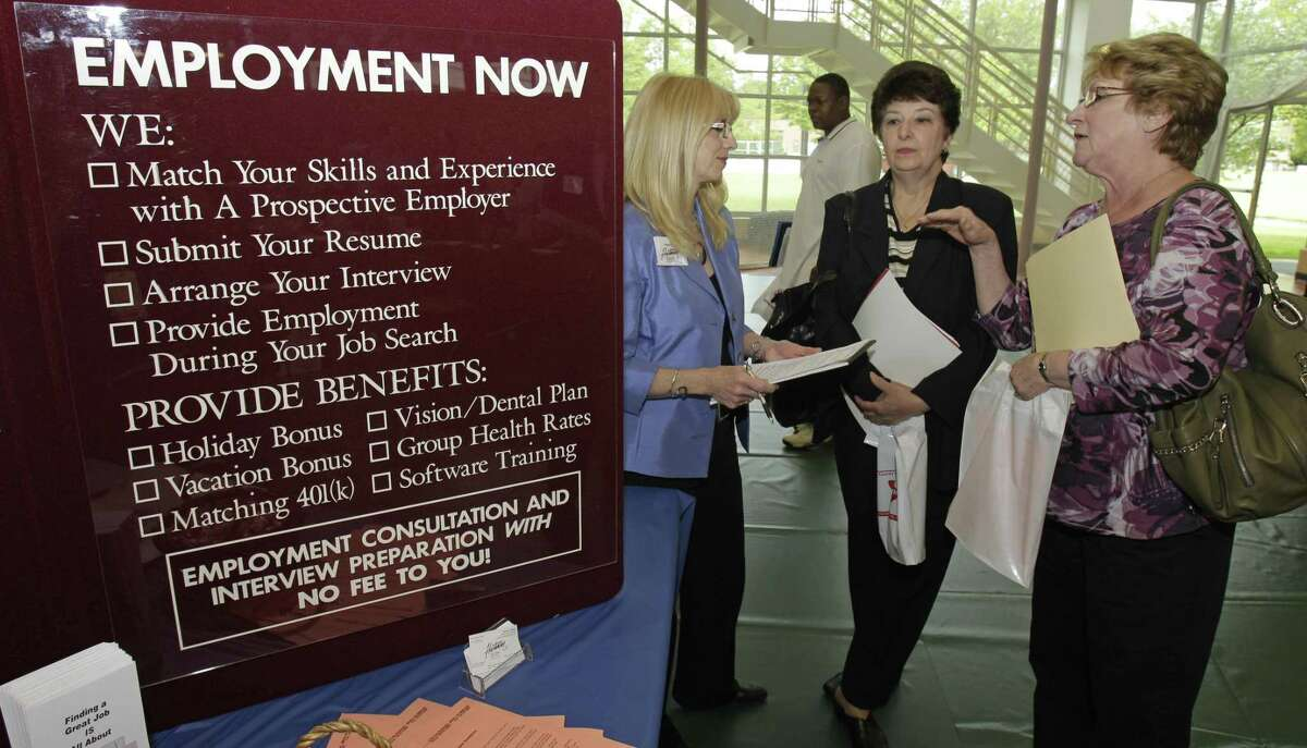 In this May 25 photo, Glynis Davies, left, from Hartman Personal Services, talks with job seekers Christine Marciante and Maxine Janke at the Jobapalooza job fair at Lake Erie College in Ohio. Fewer people sought unemployment benefits last week, though applications remain stuck at high levels that signal weak job growth. (AP Photo/Tony Dejak)