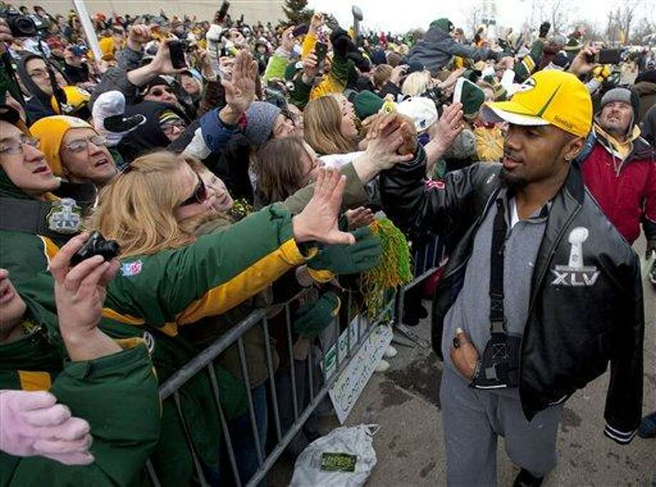 Green Bay Packers cornerback Charles Woodson high-fives fans as the NFL football team returns Monday, Feb. 7, 2011, to Lambeau Field in Green Bay, Wis., the day after defeating the Pittsburgh Steelers 31-25 in Super Bowl XLV. (AP Photo/Mike Roemer) Photo: AP / FR155603 AP