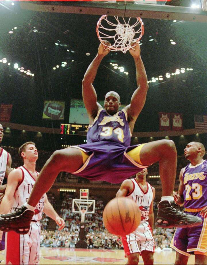 """FILE - This Nov. 12, 1996, file photo shows Los Angeles Lakers' Shaquille O'Neal (34) hanging from the rim after a dunk during the third quarter against the Houston Rockets,  in Houston.  O'Neal says on Twitter that he's """"about to retire."""" (AP Photo/David J. Phillip, File) Photo: AP / AP1996"""