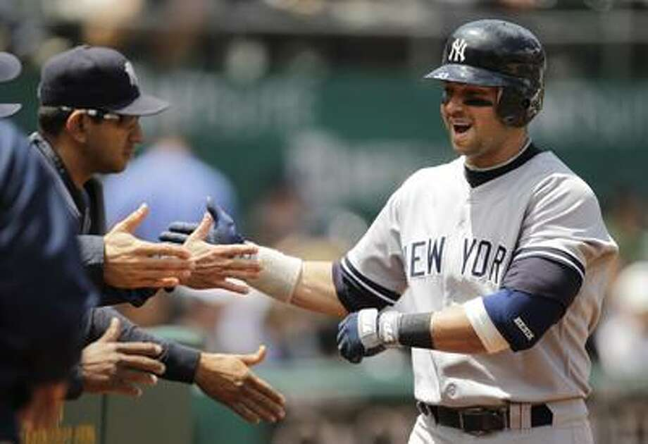 New York Yankees' Nick Swisher is greeted at the dugout after hitting  a three-run home run off Oakland Athletics pitcher Gio Gonzalez during the fourth inning of a baseball game Wednesday, June 1, 2011, in Oakland, Calif. (AP Photo/Ben Margot) Photo: AP / AP