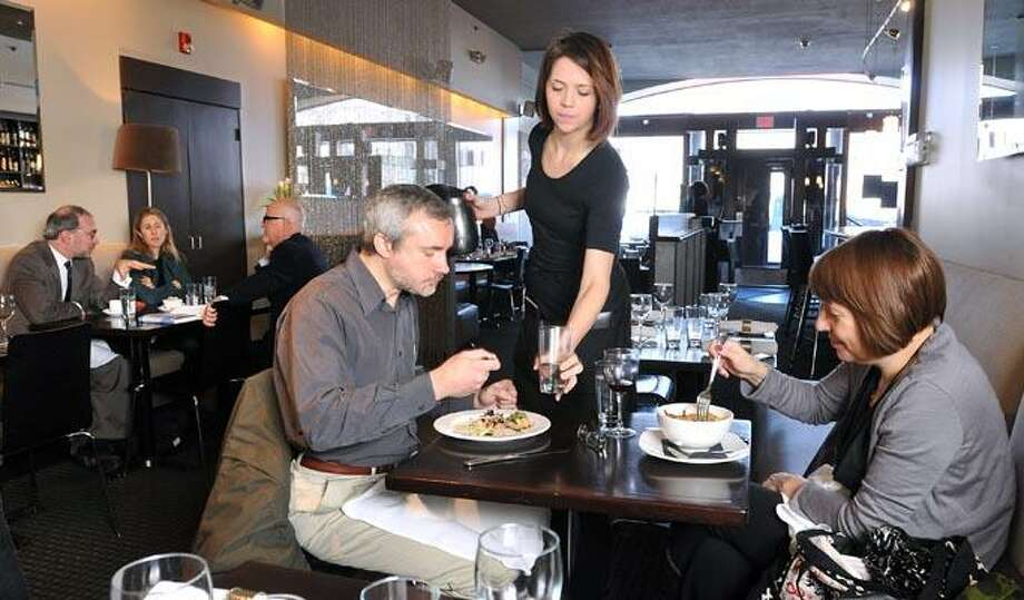 Vadim Staklo of New Haven and Alyson Waters of Brooklyn, NY., enjoy lunch as waitress Ingrid Birks tends to them at Zinc in New Haven. (Photo by Peter Casolino/New Haven Register)  02/03/11 Cas110203