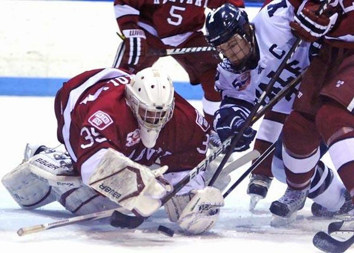 New Haven--Yale's Jimmy Martin battles for the puck with Harvard goalie Ryan Carroll. Photo by Brad Horrigan/New Haven Register-02.04.11.